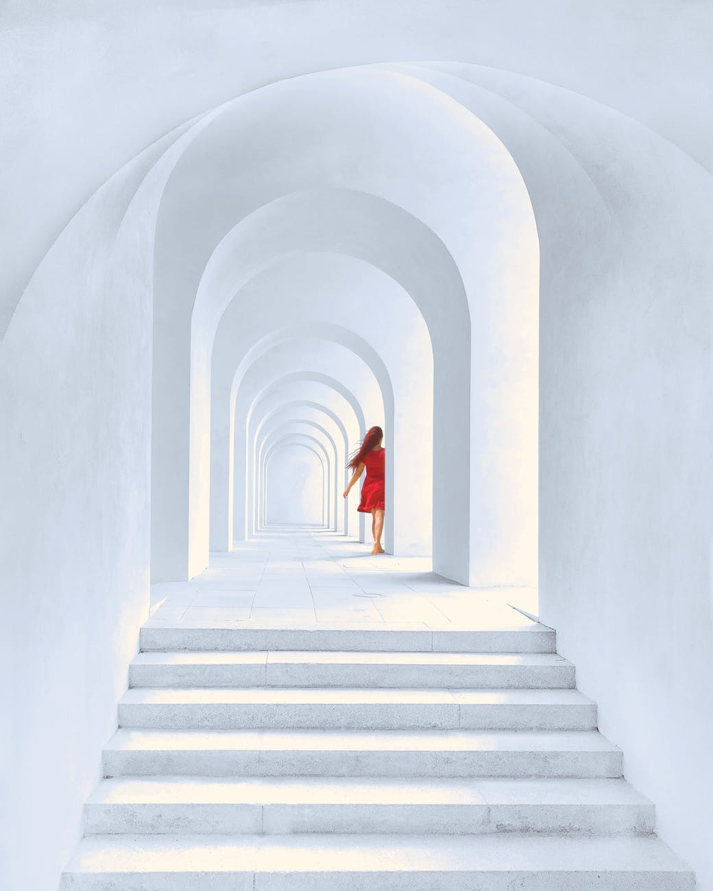 woman in red dress standing in white arch building